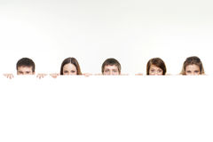 A group of teenagers hiding behind a white banner Stock Images
