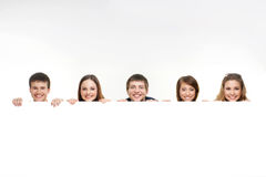 A group of teenagers hiding behind a white banner Royalty Free Stock Photography