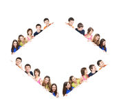A group of teenagers hiding behind a white banner Stock Photography