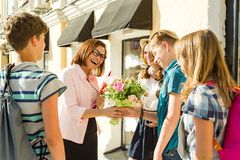 Group teenagers of high school students congratulate their teacher with bouquet of flowers. Teacher`s Day
