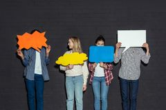 group of teenagers holding blank speech bubbles stock photography