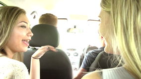 Group Of Teenagers Inside Car Driving Along Road stock footage