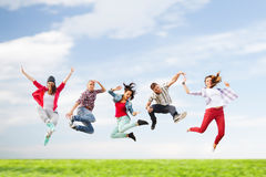 Group of teenagers jumping. Summer, sport, dancing and teenage lifestyle concept - group of teenagers jumping Stock Photos