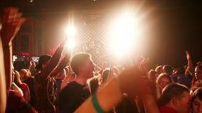 Group of teenagers jumping off a disco hands holding up under the lights flash stock footage