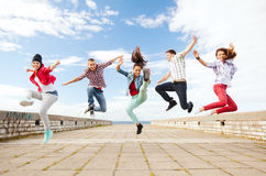 Group of teenagers jumping. Summer, sport, dancing and teenage lifestyle concept - group of teenagers jumping Stock Image