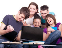 Group of  teenagers with laptop. Group of smiling teenagers looking at laptop Royalty Free Stock Images