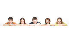 A group of teenagers leaning on a white banner Royalty Free Stock Image