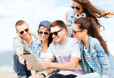 Group of teenagers looking at tablet pc Royalty Free Stock Images