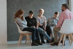 A group of teenagers looking at a withdrawn, lacking self-esteem girl. A group of teenagers looking at a withdrawn, lacking self-esteem young girl during a royalty free stock photography