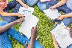 Group of teenagers making school tasks seated on the grass. Scho. Ol and friendship concept. Notebooks detail Royalty Free Stock Image