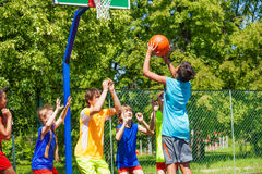 Group of teenagers play basketball on playground. Group of teenagers playing basketball on playground during summer Stock Image