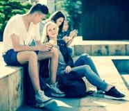 Teenagers play in smartphones in schoolyard Royalty Free Stock Photos