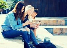 Teenagers play in smartphones in schoolyard Royalty Free Stock Photo