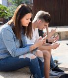 Teenagers play in smartphones in schoolyard royalty free stock images