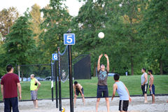 Group of teenagers playing beach volleyball game Stock Photo
