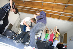Group of teenagers (16-18) playing in garage band, low angle view Royalty Free Stock Photo