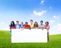 Group of teenagers posing with a white board. On the hills Royalty Free Stock Photography