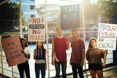 Group of teenagers protesting together. Group of teenagers protesting demonstration holding posters antiwar justice peace concept stock image