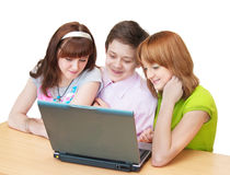 Group of teenagers - pupils having fun on laptop. Group of young students - pupils having fun on laptop Stock Image