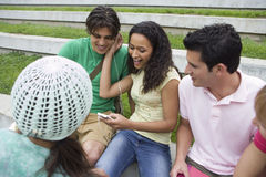 Group of teenagers (17-19) relaxing, couple listening to MP3 player, sharing headphones Stock Photos