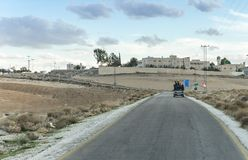 A group of teenagers riding in the open body of the tender on the suburban road near Madaba city in Jordan stock photo