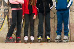 Group of teenagers in roller skates standing. Beside the wall on cloudy autumn day royalty free stock photos