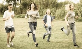 Teenagers running through green lawn in summer in park Royalty Free Stock Photo