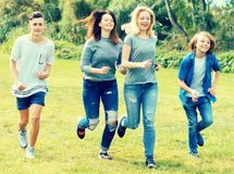 Teenagers running through green lawn in summer in park Royalty Free Stock Images