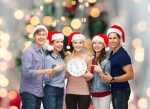 Group of teenagers in santa helper hats with clock Royalty Free Stock Image