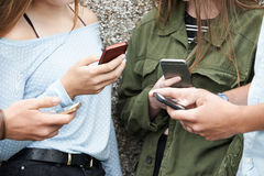 Group Of Teenagers Sharing Text Message On Mobile Phones stock image