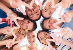 Group of teenagers showing finger five gesture. Summer, holidays, vacation, happy people concept - group of teenagers looking down and showing finger five Stock Photos