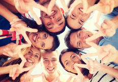 Group of teenagers showing finger five gesture. Summer, holidays, vacation, happy people concept - group of teenagers looking down and showing finger five Stock Photography
