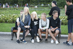 Group of teenagers sitting on the bench. Girls sit on lap of boy Stock Photography