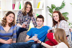 Group of teenagers sitting on sofa at home. Group of teenagers sitting on sofa in living room, drinking and talking Royalty Free Stock Photo