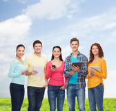 Group of teenagers with smartphones and tablet pc Stock Images