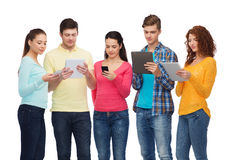 Group of teenagers with smartphones and tablet pc Stock Photos