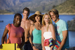 Group of teenagers (17-19) standing near lake, smiling, portrait Royalty Free Stock Images