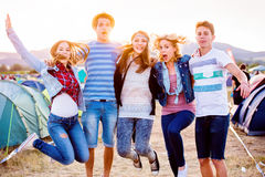 Group of teenagers at summer music festival, jumping. Group of teenage boys and girls at summer music festival, jumping, sunny day Royalty Free Stock Photos