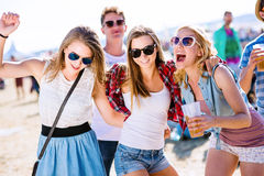 Group of teenagers at summer music festival, sunny day Stock Image