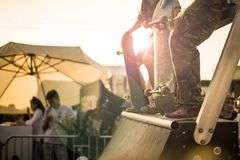 Group of teenagers with their skateboards on the ramp taking part in competition during a sunset stock photo