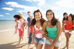 Group of teenagers walking along beach. Smiling stock image