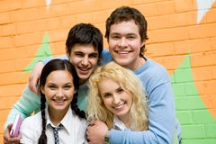 Group of teens. Portrait of glad friends in casual clothes looking at camera on background of brick wall Stock Images