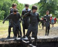 A group of teens attempt to navigate an obstacle during the Mankato Mud Run event Stock Photos