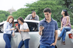 Group of teens with car. Teenagers with car and cellphones Stock Photos