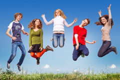 Group of teens jumping in the blue sky above the green grass Stock Photo