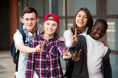 Group of teens posing outside school. Happy group of teens posing outside school with papers for study Stock Image