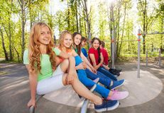 Group of teens sit on brachiating at playground Royalty Free Stock Photo