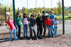 Group of teens on swingset royalty free stock photo