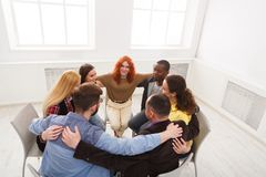 Group therapy, psychology support meeting. Group therapy. People having group hug during therapy in rehab at multiethnic psychology support meeting, copy space royalty free stock photography
