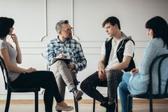Group therapy with psychologist and depressed man and woman stock photos